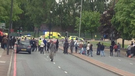 A crowd standing outside the police cordon