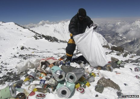 Sherpa collecting rubbish left by climbers in 2010