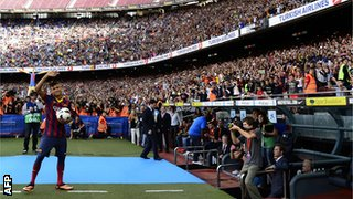 Neymar waves to the Barcelona supporters in the Nou Camp at his unveiling
