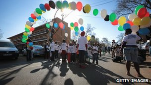 Schoolchildren arrive with balloons in tribute for former South African President Nelson Mandela outside the Mediclinic Heart Hospital where he is being treated for a recurring lung infection.
