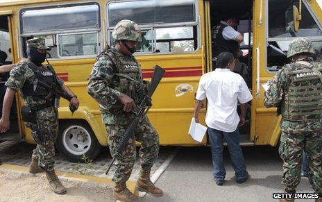 Forensic officers and Mexcian Navy personnel at a crime scene where a bus driver was killed