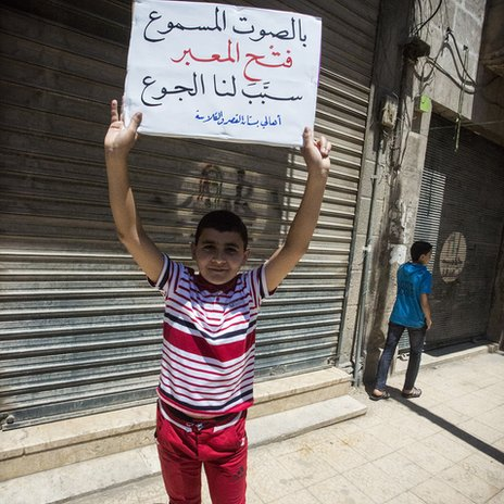 Boy holds placard demanding that the crossing point be closed