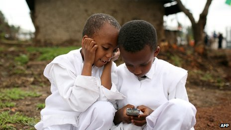 Two boys play with a mobile phone on 1 August 2008 in Debre Zeit, Ethiopia.