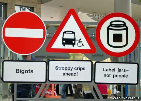 "Signs reading ""bigot"", ""stroppy crips"", ""label jars"""