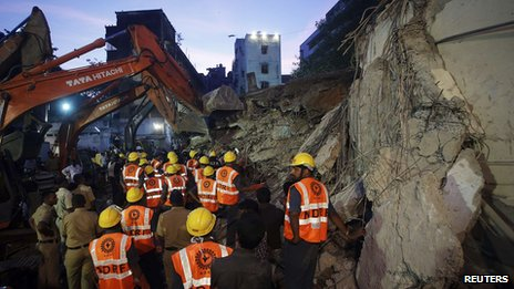 Rescue crew members search for survivors at the site of a collapsed residential building in Mumbai