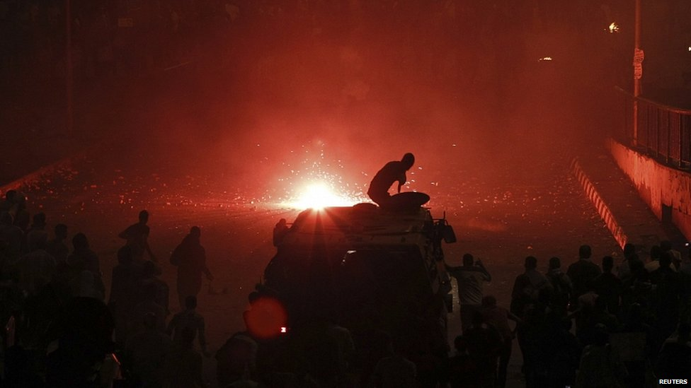 A riot police officer, on a armoured personnel carrier, takes cover as he fires rubber bullets at members of the Muslim Brotherhood and supporters of ousted Egyptian President Mohammed Morsi