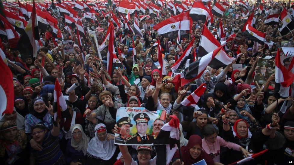 Egyptians wave national flags, and one holds a poster showing Egyptian Defense Minister Gen Sisi (C) during celebrations marking the 1973 Arab-Israeli war anniversary, in Tahrir Square, Cairo