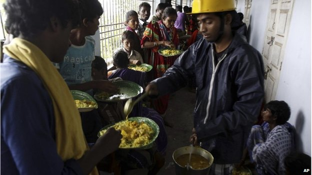 Indian villagers are given food at a shelter in Ganjam district, east of Bhubaneswar, 12 October 2013