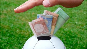 Hang pushing money into a football