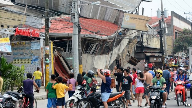 People gather on the street next to damaged buildings in Cebu city, Philippines, after a major 7.1 magnitude earthquake struck the region on 15 October 2013