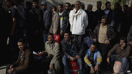 Men wait to be searched by the Syrian military