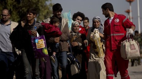 People walk from the rebel-held suburb of Moadamiya to government-held territory, helped by aid workers