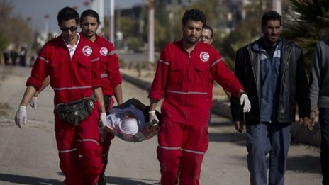 Woman held by Red Crescent workers