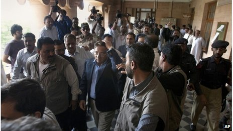 Pervez Musharraf, centre, holds his head after a shoe was thrown at him in Karachi, 29 March 2013