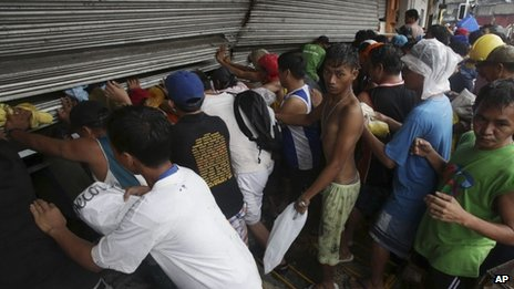 Residents in Tacloban push shutters of grocery shop in attempt to get food - 10 November