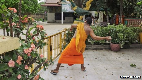 A Buddhist monk throws a stone during the protests
