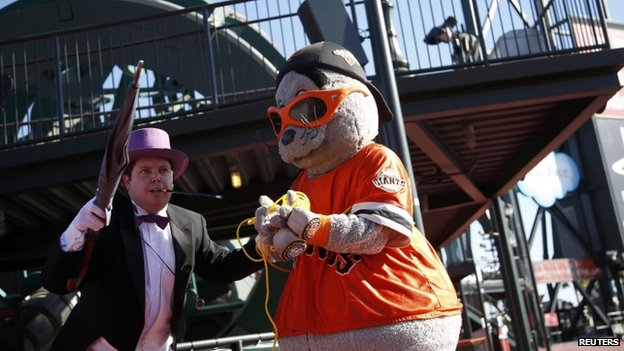 "The Penguin holds the San Francisco Giants mascot Lou Seal captive as they wait for the arrival of five-year-old leukemia survivor Miles, aka ""Batkid"" 15 November 2013"