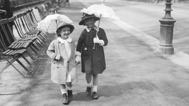 Two girls walking past park benches in 1916