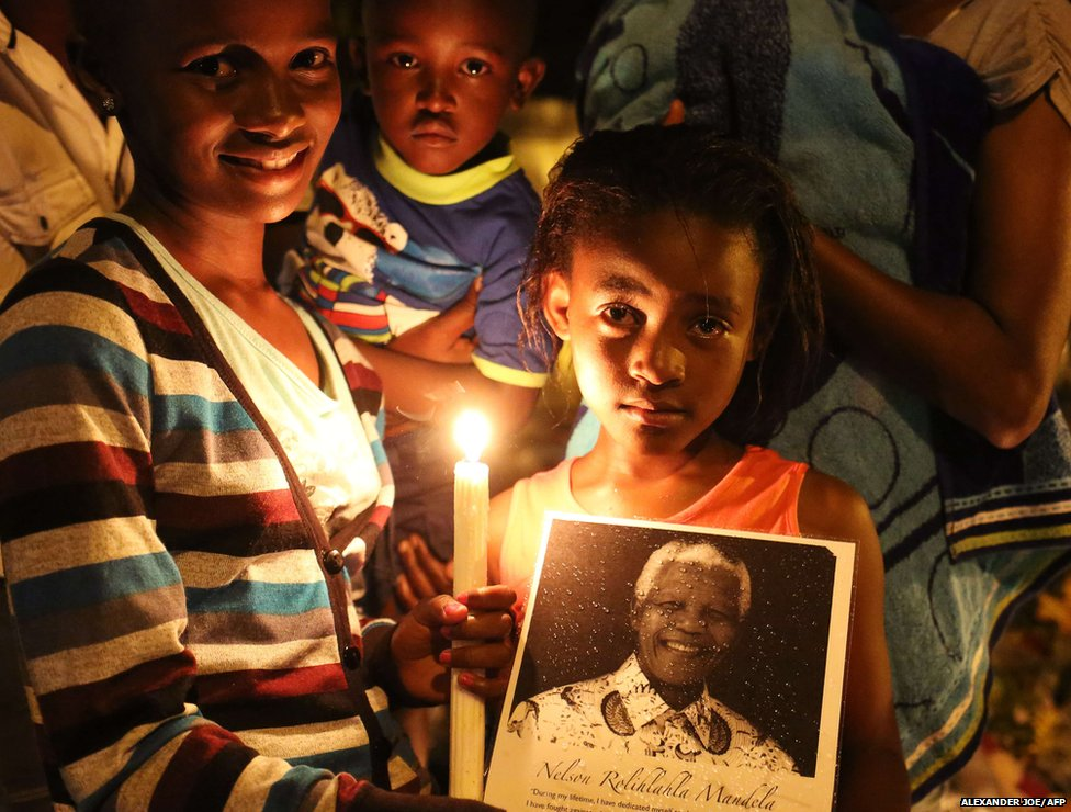 People pose with a candle in memory of late South African former president Nelson Mandela outside his home in Johannesburg