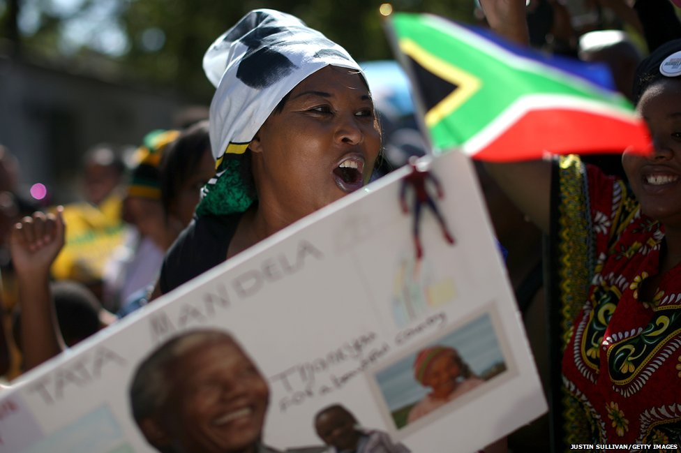 People sing and dance as they gather outside the home of former South African President Nelson Mandela