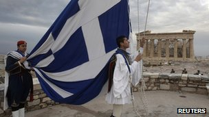 Men hoist Greek flag in front of the Parthenon temple in Athens