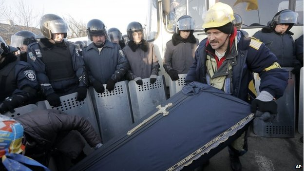 Pro-European Union activists carry a coffin symbolising the funeral of the current regime, as riot police block their approach to Ukrainian President Viktor Yanukovych's country residence of Mezhygirya outside Kiev, Ukraine, on Sunday