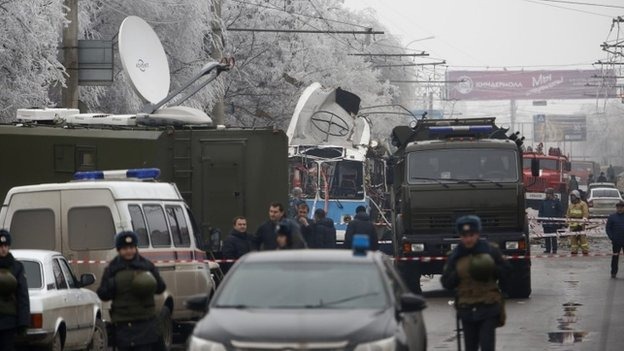 Military vehicles surround the wreckage of a trolleybus in Volgograd
