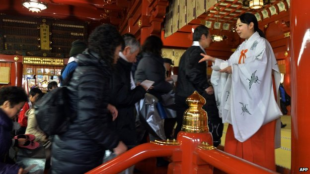A Japanese Shinto maiden (R) greets worshippers as they enter the Kanda shrine to celebrate the New Year in Tokyo on January 1, 2014