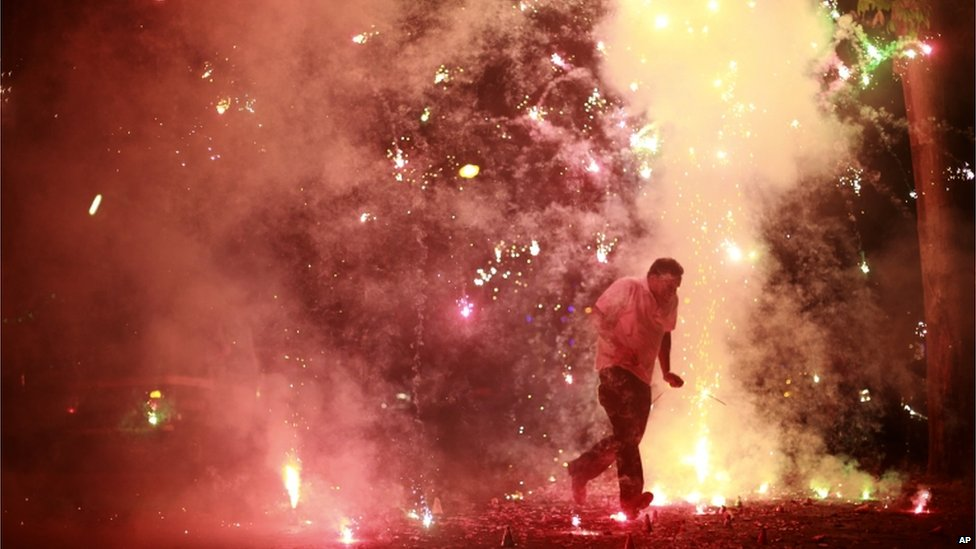 A man runs as firecrackers burst around him, on the street during the New Year celebrations in Mumbai, India, 1 January 2014