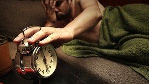 Man turns off alarm clock