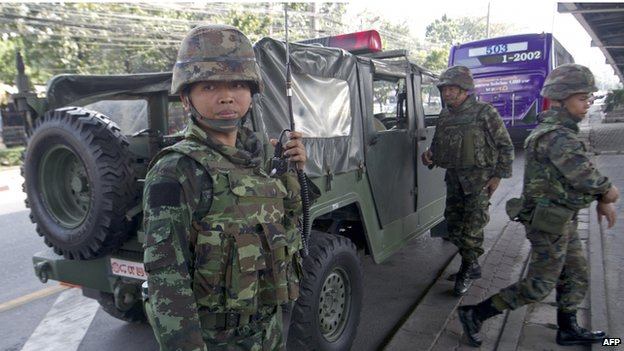 Thai soldiers stand guard at an intersection following the government's announcement of a state of emergency in Bangkok on 22 January 2014