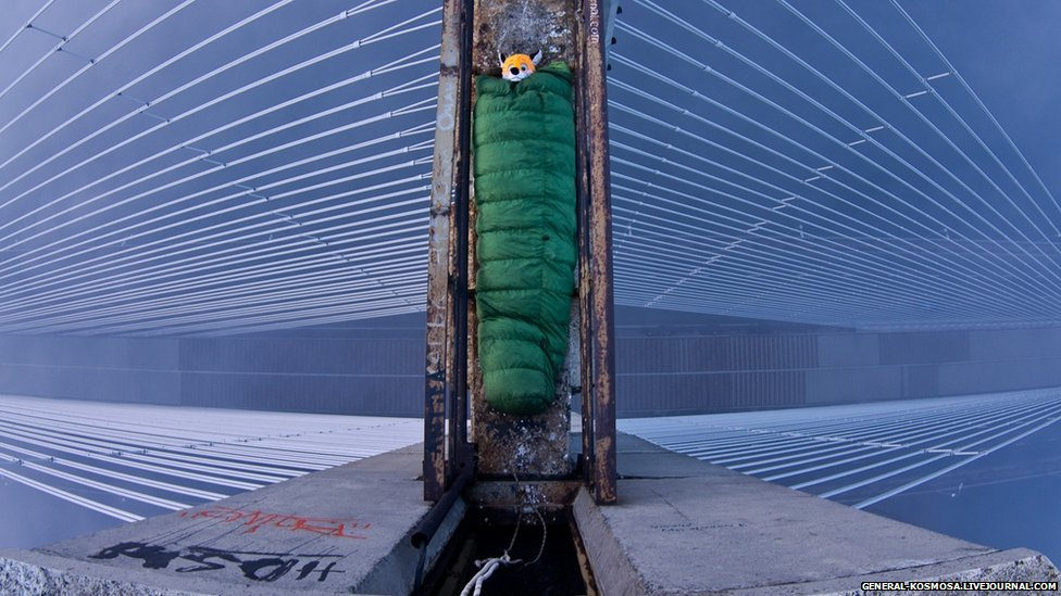 Explorer in a sleeping bag on top of a bridge.