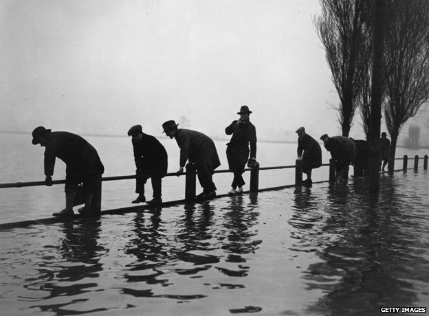Men standing on fence in flood, Lea Bridge Road 1928