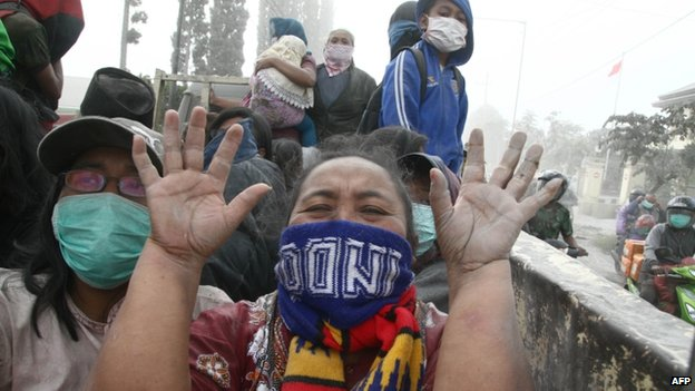 A woman gestures during the evacuation in Malang, East Java province, Indonesia, on 14 February 2014
