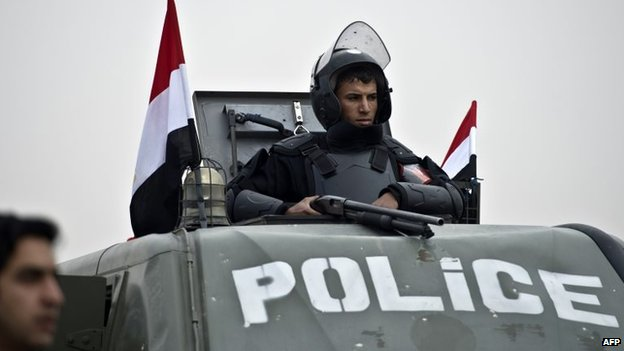 An Egyptian riot policeman stands guard on the top of an armoured vehicle outside the Police Academy