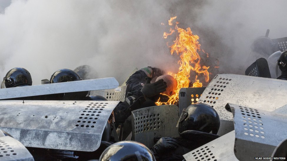 Interior Ministry members are on fire as they stand guard during clashes with anti-government protesters in Kiev