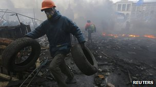 An anti-government protester carries tyres through the rubble after violence erupted in the Independence Square in Kiev February 20, 2014