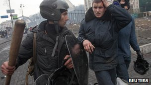 Picture shows anti-government protesters detaining a wounded policeman in Kiev, Ukraine.