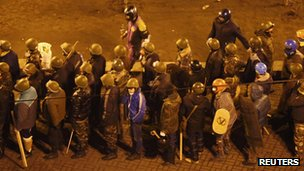 Anti-government protesters stand in line near Independence Square in central Kiev on 20 February 2014.