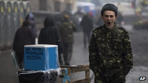 "A Ukrainian man wearing camouflage uniform yawns as he asks for donations to support the Ukrainian military with the slogan on box reading ""collecting money for Cossacks"" needs"", at Kiev's Independence Square, Ukraine on 4 March 2014."