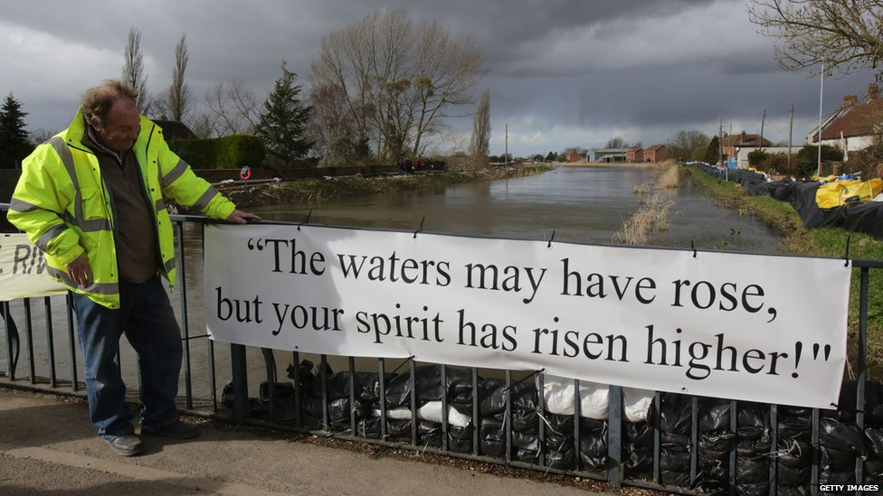 A resident looks at a banner that has been put on the bridge at Burrowbridge