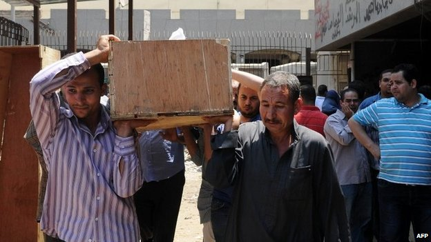Men carry the coffin of an Islamist detainee who died when tear gas was fired into a transport vehicle (19 August 2013)