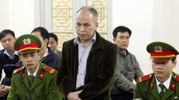 Dissident blogger Pham Viet Dao, standing at centre, appears at a court in Hanoi, Vietnam Wednesday, 19 March 2014