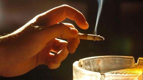 Man's hand holding lit cigarette