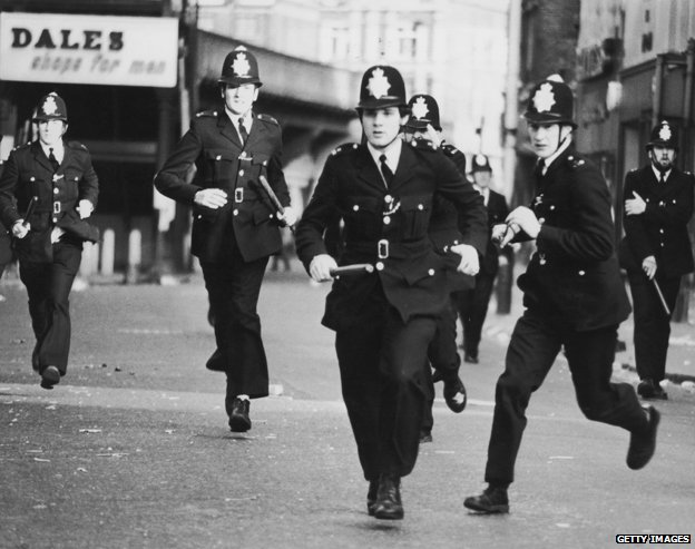 Police officers charge during the Brixton riots in 1981