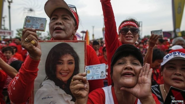 "A member of the pro-government ""red shirt"" group holds a picture of Thailand's Prime Minister Yingluck Shinawatra during a rally on the outskirts of Bangkok, 5 April 2014"