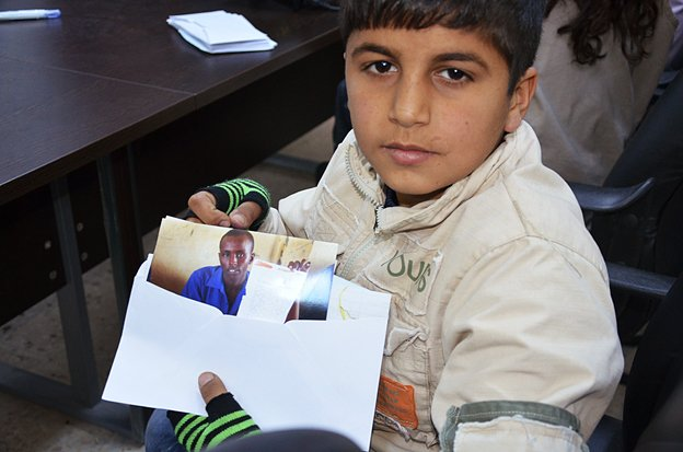 A Syrian boy holds a photo of a Somali refugee who has sent him a letter