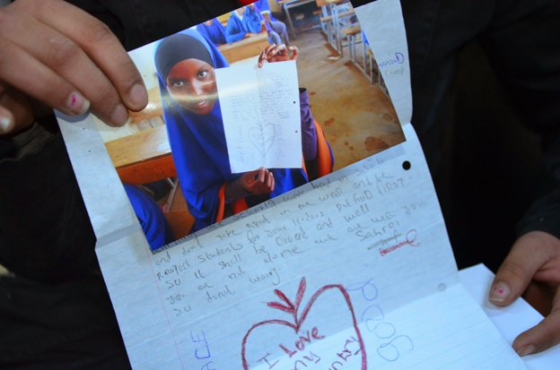 A photo of a Somali girl is held up next to her letter