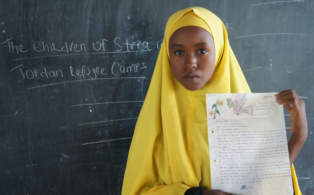 A Somali girl holds up the letter she has written