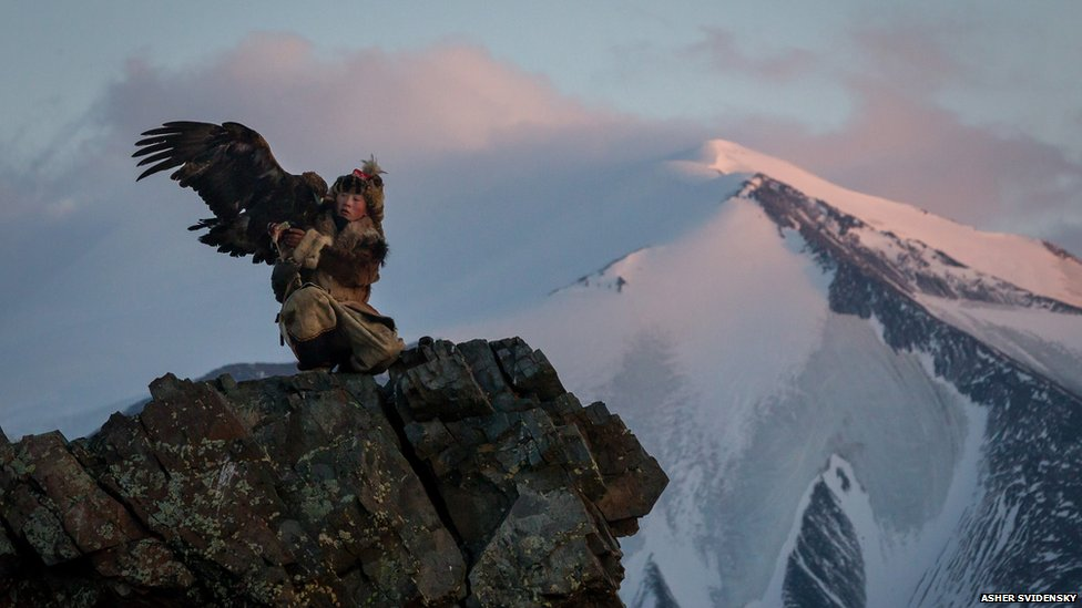 Bahak Birgen on a mountain cliff edge with his eagle